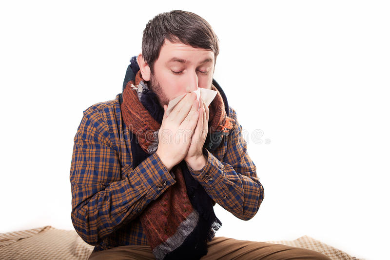 Bleke zieke mens met een griep, die op een schone achtergrond niezen royalty-vrije stock afbeelding