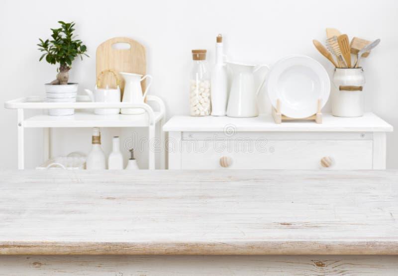 Blekt tabletop med copyspace över suddigt kökmöblemang med hjälpmedel arkivfoto