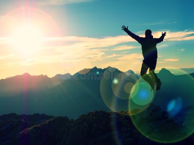 Blendenfleckeffekt Helle Kreise des Bogens Verrückter Wanderer, der an der Spitze des Berges springt stockfoto