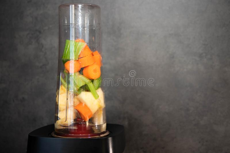 Blender with fresh vegetables. Sliced celery, apple and carrot in a blender cup for a smoothie. Healthy food. Copy space royalty free stock image