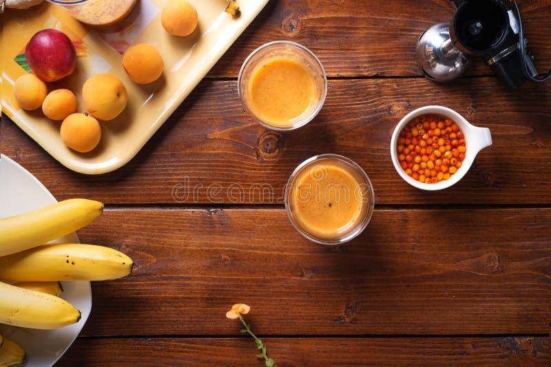 Blender kłaść przy drewnianym stołem z świeżej owoc smoothie z bananami, dennym buckthorn i morelami, Mieszkanie nieatutowy obrazy royalty free