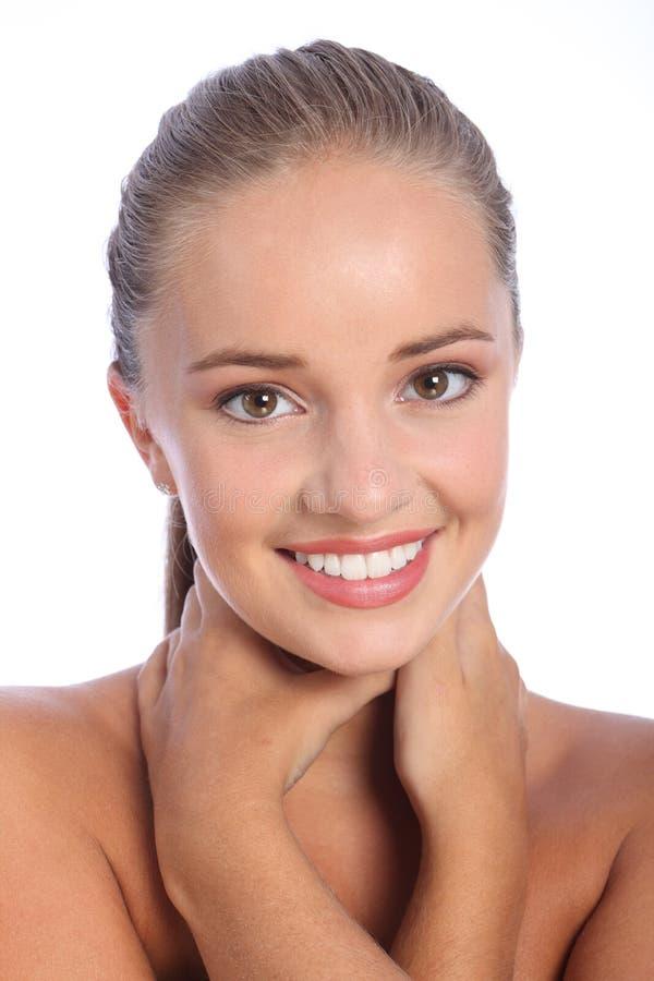 Blendunglächeln durch schöne glückliche junge Frau stockfotografie