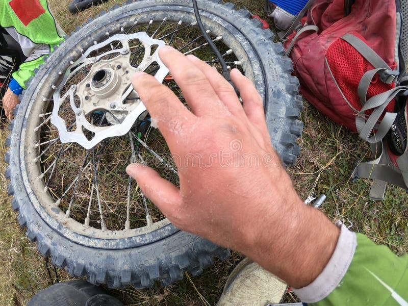 Blessure de main sur la moto et réparation de roue dans les montagnes images libres de droits