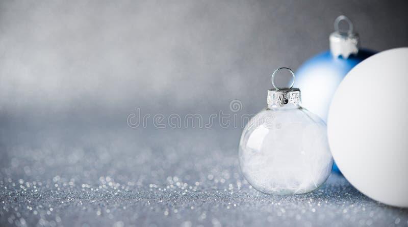 Bleu, argent et ornements blancs de Noël sur le fond de vacances de scintillement Carte de Joyeux Noël images stock