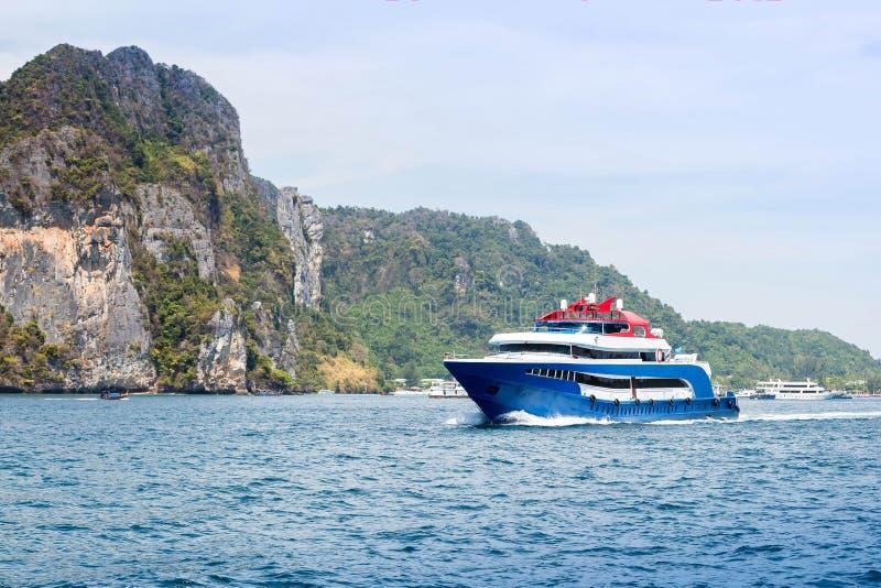 Bleu avec le bateau blanc et rouge de vitesse de plaisir d'accents Navigation sur la mer contre une île tropicale Front View images stock