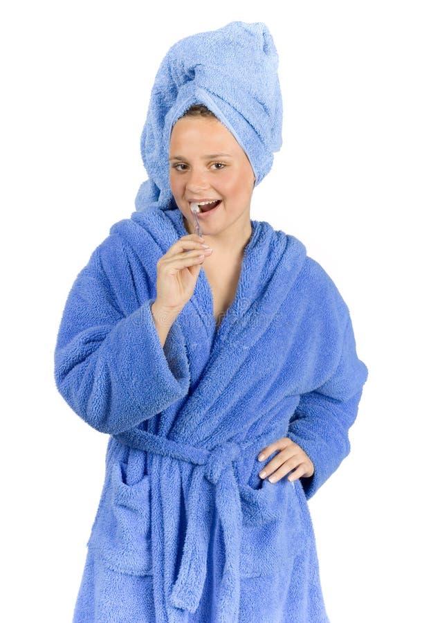 bleu de peignoir balayant les jeunes rectifiés de femme de dents photographie stock libre de droits