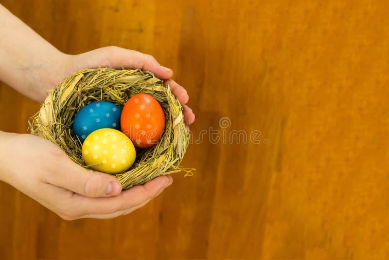 Bleu jaune-orange de trois oeufs colorés avec le modèle floral dans une carte de voeux de conception de Pâques de nid de paille a photo stock