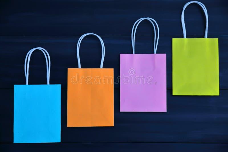 Bleu, orange, rose et sacs jaunes de cadeau sur un fond en bois foncé, diagonal image stock