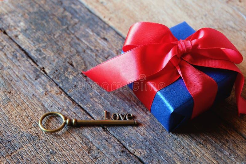 Bleu profond rougeoyant avec le boîte-cadeau rouge de ruban et aimer la forme principale sur la table en bois de cru Un présent a photos stock