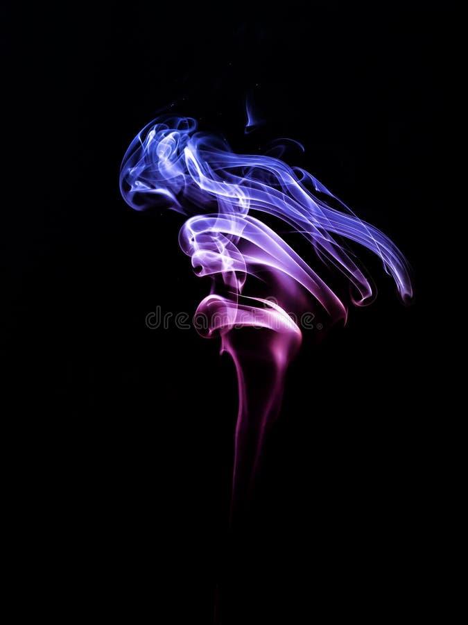 Bleu rouge de fumée sur un fond noir abrégez le fond photographie stock