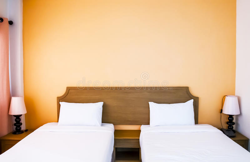 Bliźniaczy łóżka z wezgłowie lampą i stołem. zdjęcie royalty free
