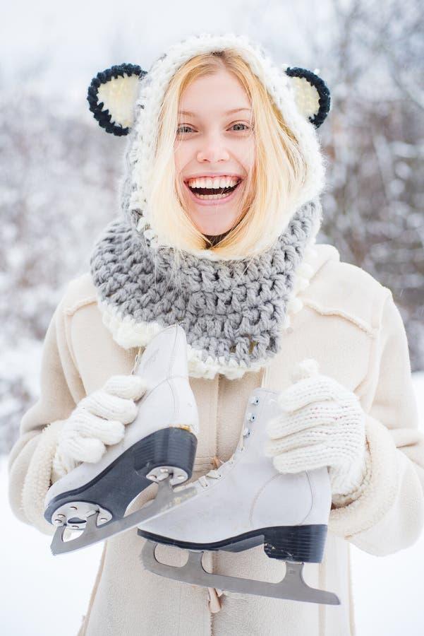 Bli Joyful Girl som har kul i vinterparken Vackra leende unga kvinnor i varma kläder med isskor Winter royaltyfria bilder