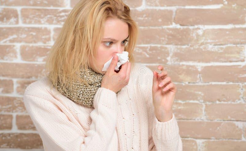 Bli opassligt med förkylning eller influensa Sjuk kvinna som rymmer febertermometern Gullig dåligt flicka som mäter kroppstempera royaltyfri foto