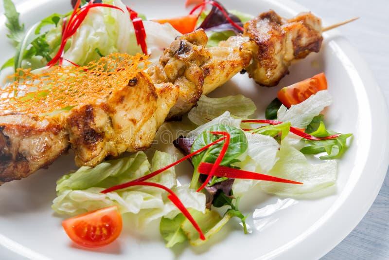Bli rädd grillat kött på pinnen med sallad och tomater på den vita plattan Slut upp med den selektiva fokusen royaltyfri bild
