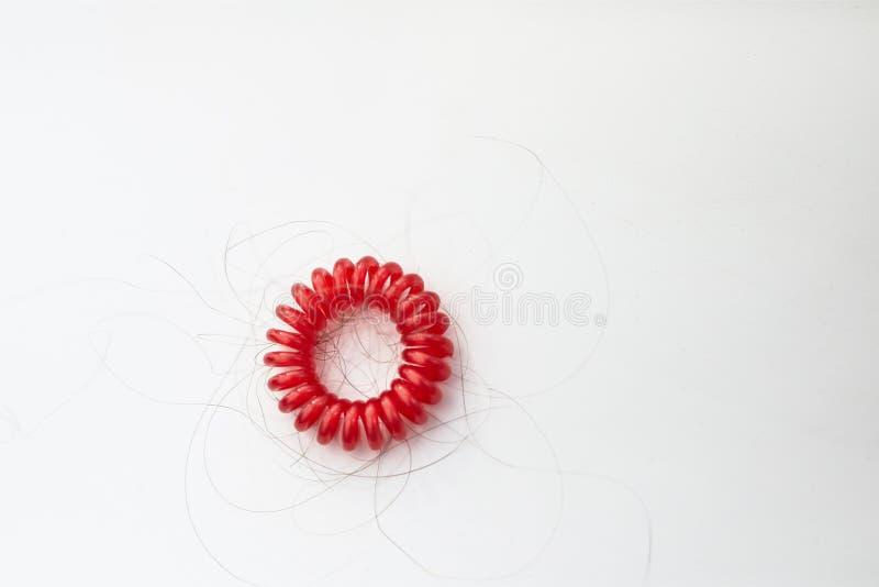 Bli skallig begreppshårförlust, rött hårband med löst hår arkivfoto