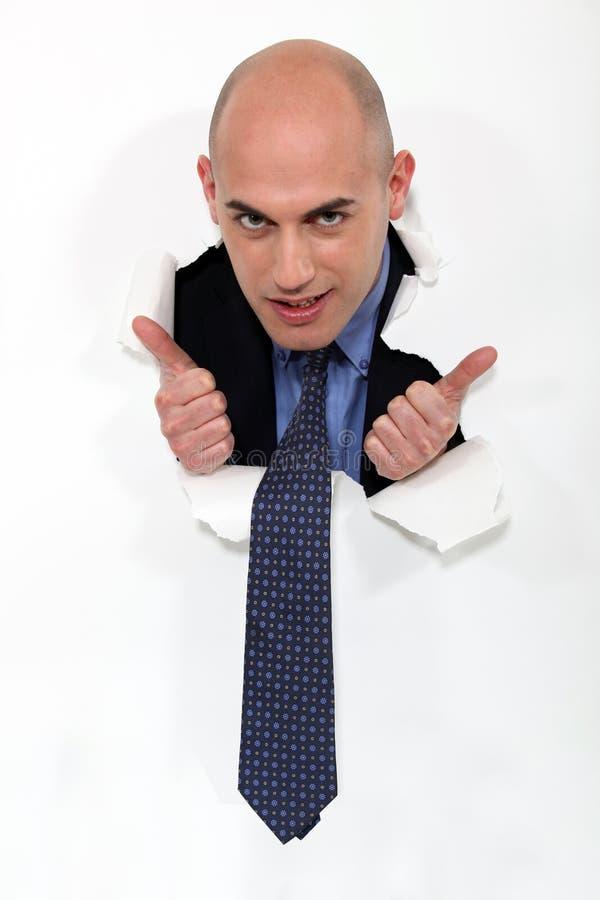 Bli skallig manen som plirar till och med pappers- royaltyfri fotografi
