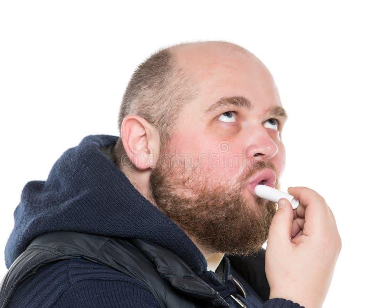 Bli skallig skäggigt fett manbruk en skyddande läppstift arkivbild