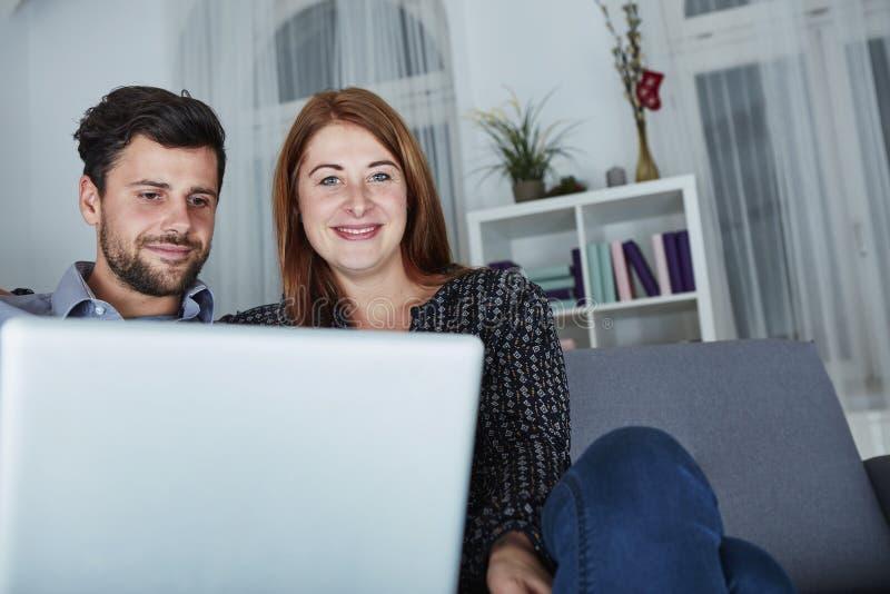 Blick des glücklichen Paars auf Laptop-PC für Weihnachten lizenzfreie stockfotos