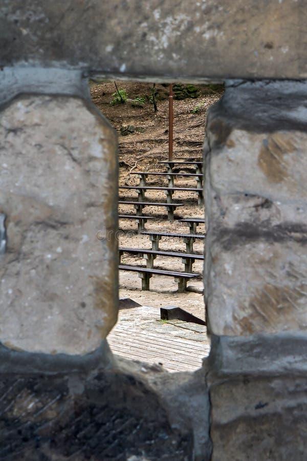 Blick des Lochs in der Steinwand auf Reihen die Holzbank, lizenzfreies stockbild