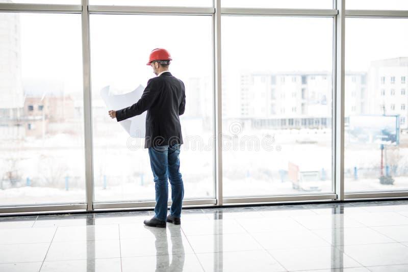 Blick för hjälm för säkerhet för byggmästareteknikerkläder på konstruktion för ritningpapper nära panorama- fönster arkivfoto