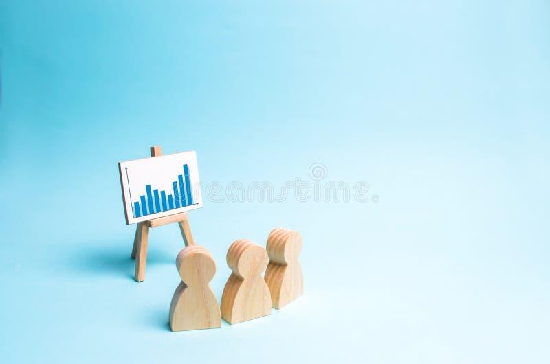 Blick för tre personer på schemat och att diskutera affärsstrategi och plan för utvecklingen av företaget analys arkivfoto