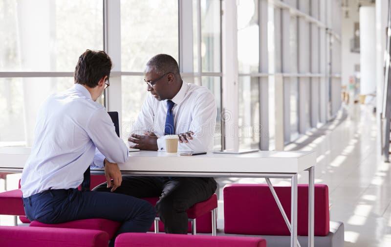 Blick för två affärsman på bärbar datorskärmen under ett möte arkivfoto