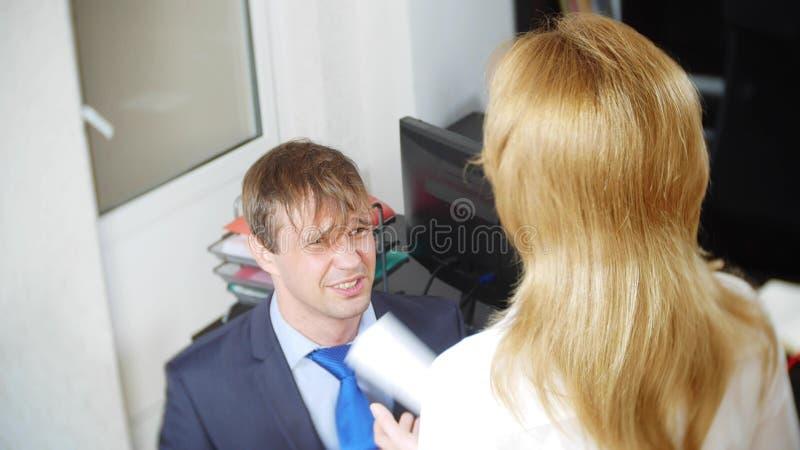 Blidka ironi, det kvinnliga framstickandet agar kontorsarbetaren som står framme av henne på hans knä, royaltyfri bild