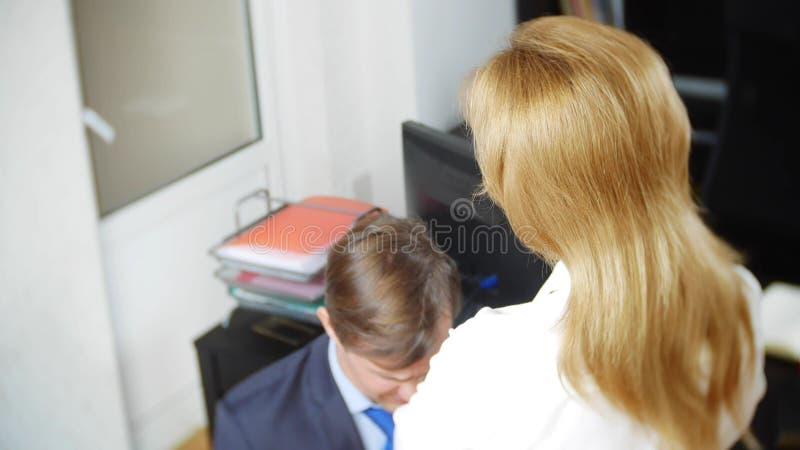 Blidka ironi, det kvinnliga framstickandet agar kontorsarbetaren som står framme av henne på hans knä, royaltyfria foton