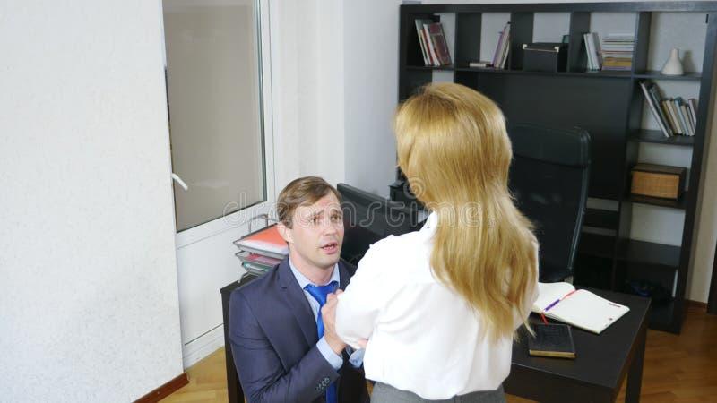 Blidka ironi, det kvinnliga framstickandet agar kontorsarbetaren som står framme av henne på hans knä, arkivbilder