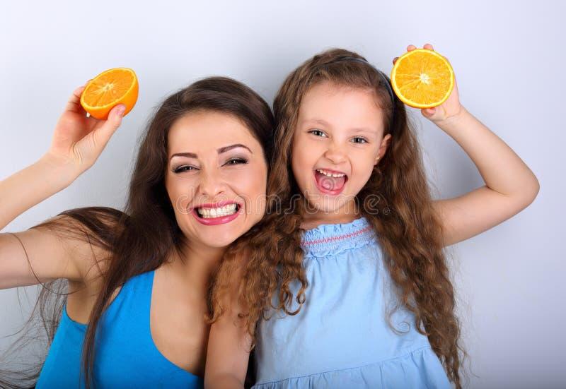 Blidka skratta barnmodern och det gulliga långa hårdotterinnehavet arkivfoton
