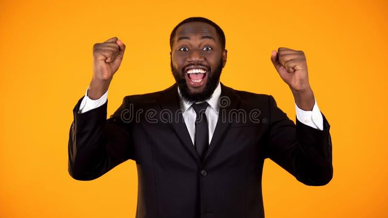 Blij Afrikaans mannetje in formalwear ja makend gebaar, succesvol opstarten, winnaar stock afbeeldingen