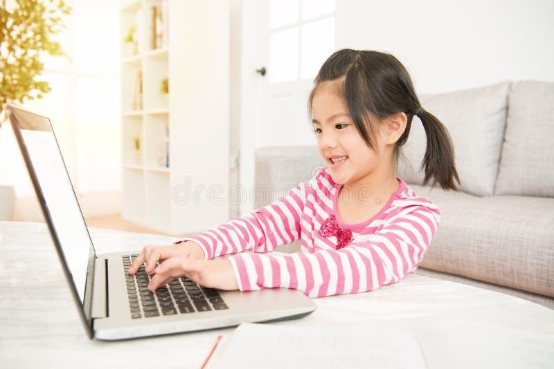 Blij Aziatisch schoolmeisje met haar computer stock foto's
