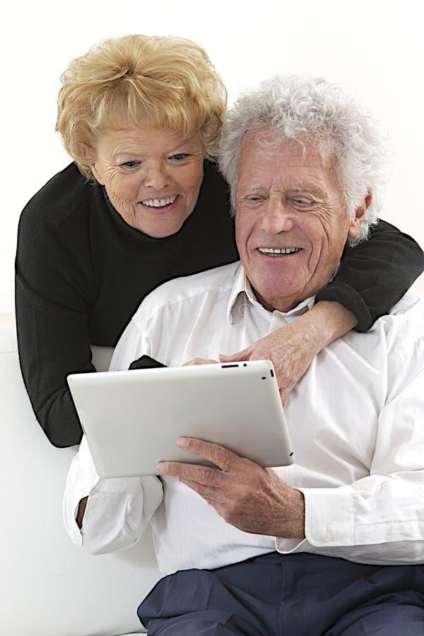 Blij bejaard paar met tablet stock foto