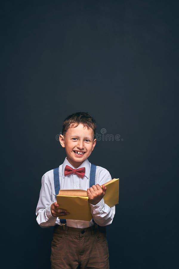Blij bevindt weinig jongen zich op een zwarte achtergrond met een boek in zijn handen een gelukkig kind leert om een boek te leze stock foto