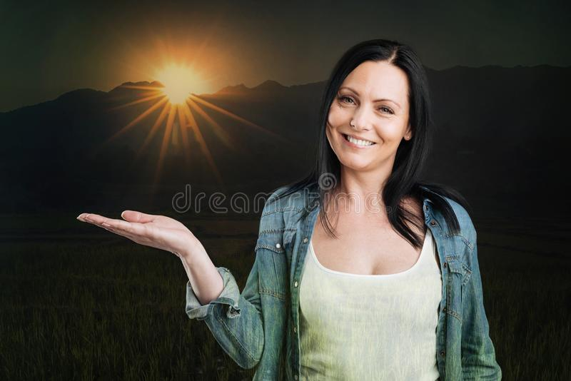 Blij brunette die terwijl het stellen met zon op haar hand glimlachen royalty-vrije stock afbeelding