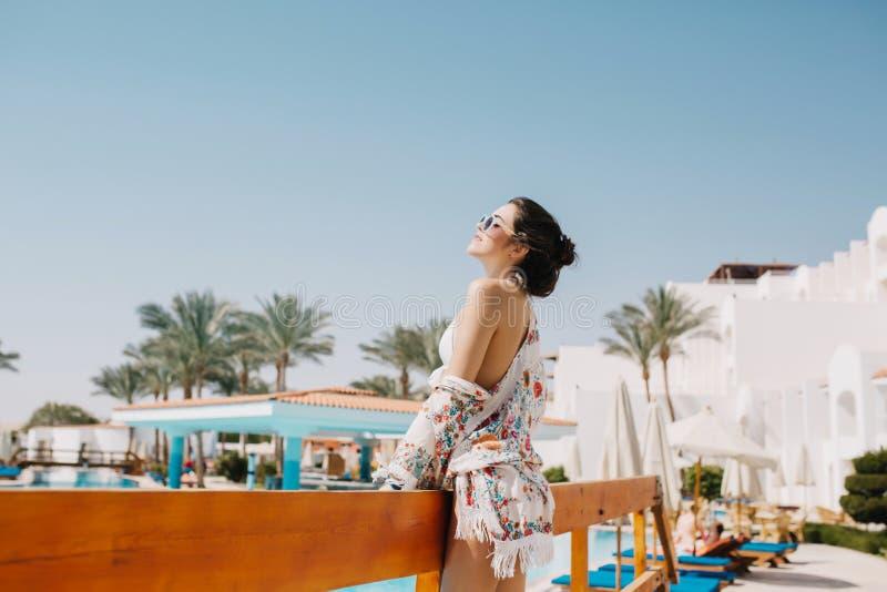 Blij donker-haired meisje die in witte kledij van verse overzeese lucht genieten die zich voor hotel bevinden Portret van dromeri royalty-vrije stock foto's