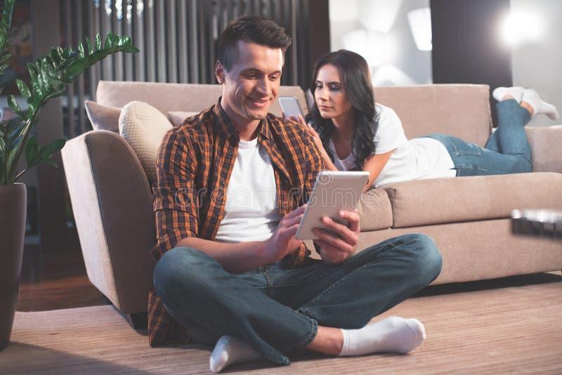 Blij echtpaar die eigentijdse technologie thuis gebruiken royalty-vrije stock fotografie