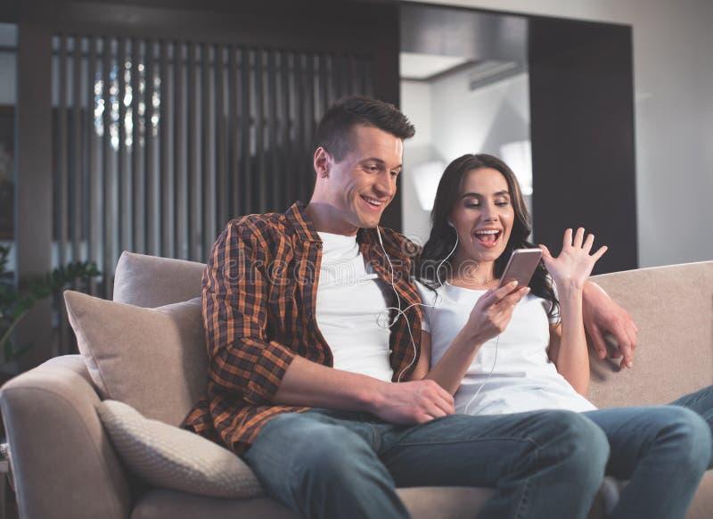 Blij echtpaar die telefoon voor online mededeling met behulp van royalty-vrije stock afbeelding