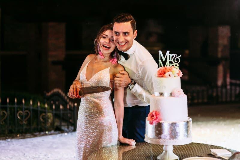 Blij enkel echtpaar naast de huwelijkscake stock afbeeldingen