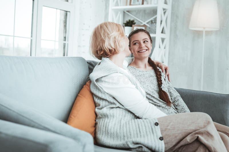 Blij gelukkig meisje en haar grootmoederzitting op de bank royalty-vrije stock afbeeldingen