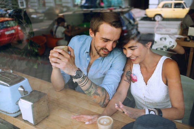 Blij glimlachend paar die in koffie achter het venster spreken royalty-vrije stock afbeeldingen