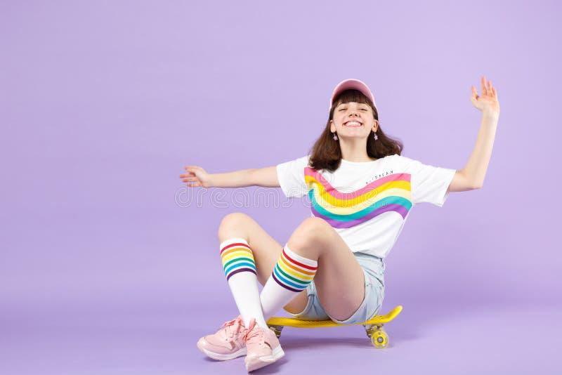 Blij glimlachend tienermeisje die in levendige kleren op geel die skateboard, het uitspreiden handen zitten op violette pastelkle royalty-vrije stock foto's