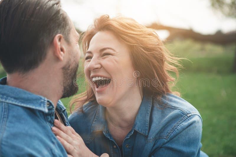 Blij houdend van paar die rust op weide hebben stock foto