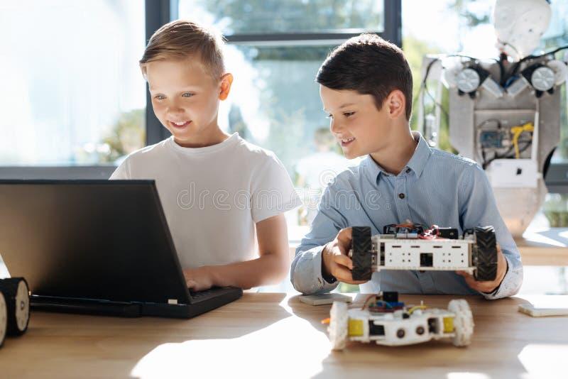 Blij jong geitje die op zijn vriendenprogramma letten een robotachtig voertuig stock foto's