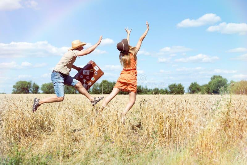 Blij jong paar die pret op tarwegebied hebben Opgewekte man en vrouw die met retro leerkoffer lopen op blauwe hemel royalty-vrije stock afbeelding