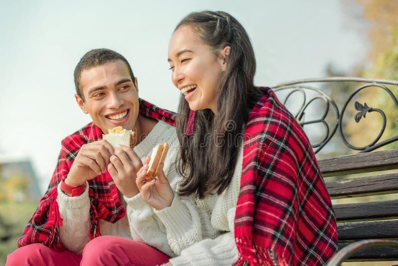 Blij knap paar die freshly-made sandwiches op een bank eten royalty-vrije stock foto