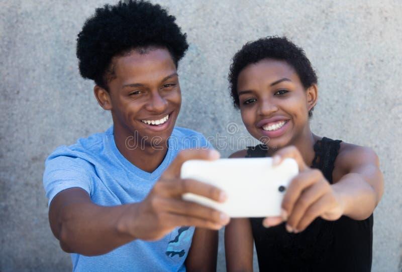 Blij lachend Afrikaans Amerikaans paar die selfie met telefoon nemen stock afbeeldingen