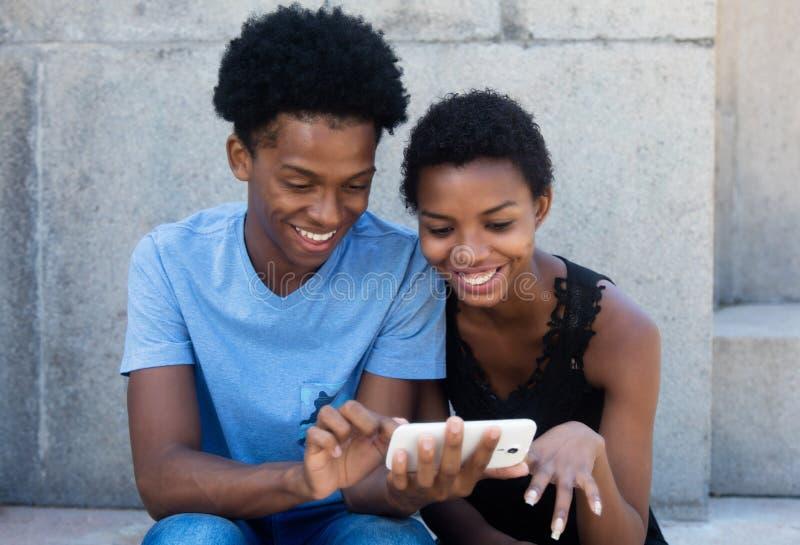 Blij lachend Afrikaans Amerikaans paar die telefoon bekijken royalty-vrije stock afbeelding