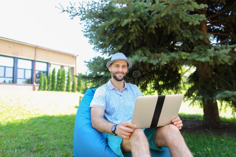 Blij maak kerel lettend op levende stroomvoetbalwedstrijd door laptop in zak stock foto's