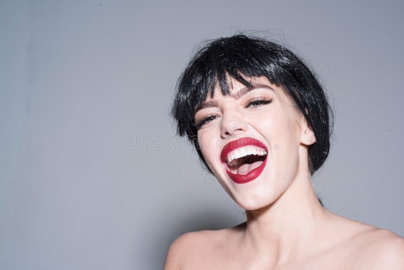 Blij meisje die met volledige rode lippen, vrijheidsconcept schreeuwen Gelukkige jonge vrouw in zwarte die pruik op grijze achter royalty-vrije stock fotografie